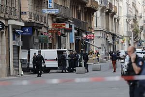French police secure a perimeter after a suspect package explodes in Lyon.