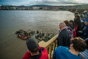 People watch a military minesweeper at a Margaret Bridge pier, as operations get under way to recover the capsized boat.