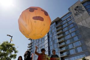 Demonstrators hold an inflatable angry emoji during a protest outside the Facebook meeting.