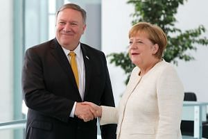 Pompeo and German Chancellor Angela Merkel shake hands during a joint news conference.