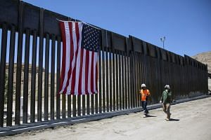 Construction workers walk past a new barrier on the border with Mexico, on May 28, 2019.