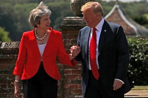 Britain's Prime Minister Theresa May and US President Donald Trump walk to a joint news conference at Chequers, Britain, on July 13, 2018.