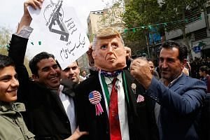 Iranians pretending to strike a man wearing a mask of President Donald Trump during an anti-US rally in Teheran in April.