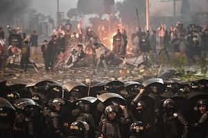 Indonesian police taking a barrage of rocks, fireworks, Molotov cocktails and other projectiles from rioters during a riot outside election supervisory agency Bawaslu's headquarters in downtown Jakarta on May 22. The violence peaked in the evening th