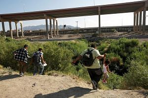 Migrants making an illegal crossing last week from Ciudad Juarez in Mexico to the United States, where they planned to turn themselves in to request asylum in El Paso, Texas. Talks between the US and Mexico were slated to kick off yesterday with a me