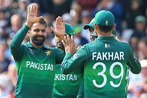 Pakistan's Mohammad Hafeez (left) celebrates with teammates after taking the wicket of England's captain Eoin Morgan during the 2019 Cricket World Cup group stage match between England and Pakistan at Trent Bridge in Nottingham, central England, on J