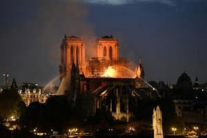 Firefighters douse flames rising from the roof at Notre-Dame Cathedral in Paris on April 15, 2019.