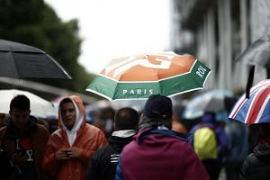 Spectators walk around at Roland Garros, as no matches are played due to rain.