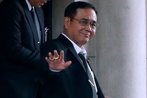 Prayut Chan-o-cha waves to the media as he leaves Government House in Bangkok, June 5, 2019.