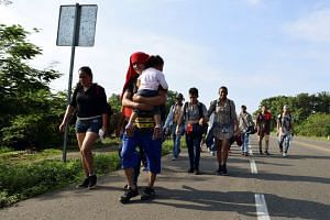 Migrants from Central America walk on a highway during their journey towards the US, June 5, 2019.