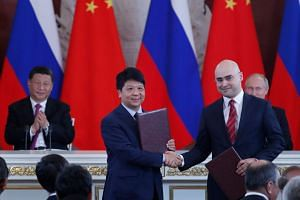 Chinese President Xi Jinping (left) and Russian President Vladimir Putin (right) applaud as Guo Ping (second left), deputy chairman of the board and rotating chairman of Huawei, shakes hands with Alexei Kornya (second right), president and CEO of Rus