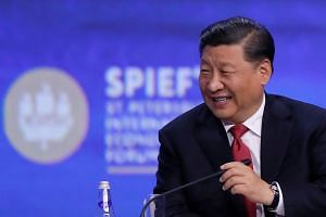 Xi Jinping reacts during a session of the St. Petersburg International Economic Forum.