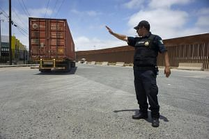 A city policeman directs traffic for a line of trucks as they wait in line to enter the commercial border inspection station in Tijuana, Mexico, on June 4, 2019.