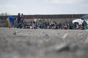 Migrants wait to be processed and loaded onto a bus by Border Patrol agents after being detained when they crossed illegally into the US from Mexico on June 2, 2019.