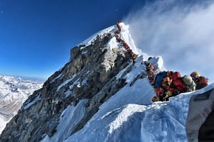 Mountain climbers line up to stand at the summit of Mount Everest.