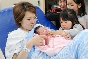 A Japanese mother holds her newborn baby while her family members look on at a hospital in Izumi city, Osaka, on May 1, 2019.