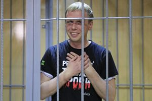 Golunov is held inside a defendants' cage as he attends a court hearing in Moscow.