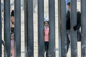 A girl waving to onlookers through the fence at the US-Mexico border wall at Friendship Park in San Ysidro, California, in November last year. Frustrated by a recent surge of migrants that has overwhelmed US resources on its southern border, Presiden