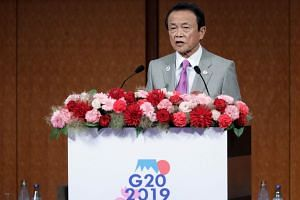 Japan's Finance Minister Taro Aso speaks at a seminar during the G-20 finance ministers and central bank governors meeting in Fukuoka on June 8, 2019.
