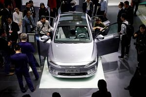 People try out Geely's new electric vehicle Geometry A during the Shanghai auto show on April 16, 2019.