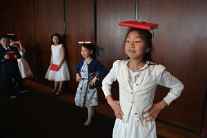 Danielle Liu (second, right) and Sofia Gao (right) trying to balance books on their heads as they walk during an etiquette and manners class in central Shanghai on June 1, 2019.