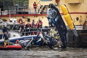 A helicopter that crashed in the Hudson River in New York City is pulled out of the water on May 15, 2019. The pilot, who was the only person aboard the helicopter, survived the incident.