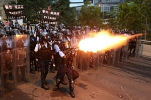 Police officers fire tear gas during a demonstration against a proposed extradition bill in Hong Kong on June 12, 2019.