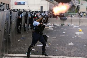 Police officer fires tear gas at protesters during a demonstration against a proposed extradition bill in Hong Kong, China on June 12, 2019.