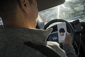 A Beijing cabby scanning his face to access an application on his smartphone. Since 2015, facial recognition technology has been used in China in fields such as government affairs, finance and retail. PHOTO: BLOOMBERG