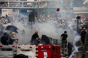 Protesters react to tear gas during a demonstration against a proposed extradition Bill in Hong Kong on June 12, 2019.