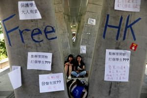 People on June 14, 2019, sitting next to posters and signs placed following protests against the proposed extradition Bill in Hong Kong.