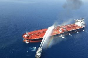 An Iranian navy boat trying to control fire from the Norwegian-owned Front Altair tanker, which is said to have been attacked in the waters of the Gulf of Oman on June 13, 2019.