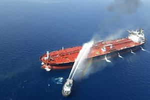 An Iranian navy boat tries to stop the fire of an oil tanker after it was attacked in the Gulf of Oman, on June 13, 2019
