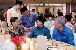 Minister-in-charge of Muslim Affairs Masagos Zulkifli (in purple) with (seated, from left) Deputy Prime Minister Heng Swee Keat, Mufti Fatris Bakaram and Senior Minister Teo Chee Hean at a Hari Raya get-together for community and religious leaders ye