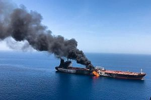 A frame grab from a video released by the US Central Command. The US says the video shows Iranians removing an unexploded limpet mine from one of the ships after the attacks. PHOTO: EPA-EFE An oil tanker after it was attacked in the Gulf of Oman, in