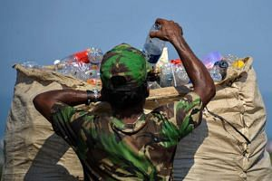 A man collecting plastic materials at a garbage dump in Banda Aceh, Indonesia.