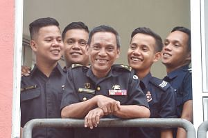 Senior Warrant Officer 1 Khairudin Mohamed Ali with his sons (from left) Khairul Azhar Khairudin, Khairul Anwar Khairudin, Khairul Ariffin Khairudin (in his Police Coast Guard uniform for in-camp training) and Muhammad Khairi Khairudin at Woodlands F