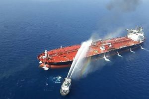 A picture from Iran's Tasnim News Agency showing an Iranian navy boat trying to control fire on the Norwegian-owned Front Altair which was attacked in the waters of the Gulf of Oman last Thursday. The US has accused Teheran of carrying out the attack