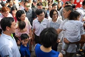 Deputy Prime Minister Heng Swee Keat (centre) and his wife (right) speak to families at the opening ceremony of Dad's Day Out 2019 at the OCBC Square of the Singapore Sports Hub.