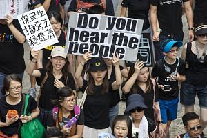 Protesters holding placards in the air while marching during a rally in Hong Kong on June 16, 2019.