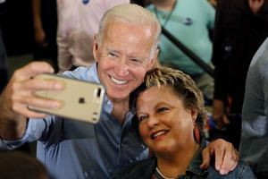 Biden, takes a selfie with a supporters during a campaign event in Iowa.