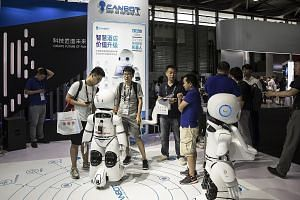 Robots produced by Beijing Kangli Youlan Robot Technology at the CES Asia trade technology show in Shanghai last week. According to the Cambrian AI Index report, China lags behind the US in basic research, training of qualified specialists, the numbe
