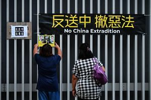 A protester hanging placards near the Lennon Wall, near Hong Kong's central government offices in Admiralty on June 18, 2019.