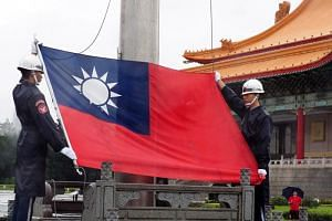 Soldiers hoist Taiwan's national flag at Liberty Square in Taipei on June 14, 2019.