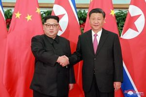 North Korean leader Kim Jong-un (left) shakes hands with Chinese President Xi Jinping during their meeting in Dalian, China, on May 8, 2018.