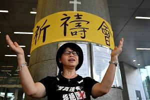 A protester singing Sing Hallelujah To The Lord at the Legislative Council Complex yesterday. The hymn has caught on quickly for its simple tune and lyrics, and is constantly being sung across protest sites.