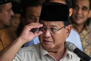 Indonesia's presidential challenger Prabowo Subianto adjusts his glasses during a press conference in Jakarta on May 21, 2019.