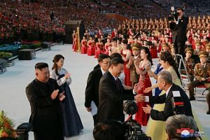 North Korean leader Kim Jong Un and wife Ri Sol Ju look on as China's President Xi Jinping and his wife Peng Liyuan are greeted by performers at a mass display in this undated photo released on June 21, 2019.
