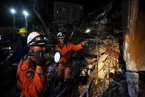 Rescue workers search for victims in the debris after an under-construction building collapsed in Sihanoukville.