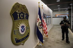 A law enforcement officer walks past ICE logo at the US Immigration and Customs Enforcement headquarters in Washington in 2017.
